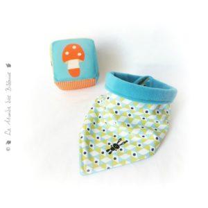 Bavoir bandana bébé .motifs géométrique .Réversible doublé micropolaire bleu turquoise.