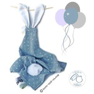 Doudou  oreilles de lapin, tissu double gaze de coton bleu jean motif étoiles blanches avec attache sucette ,multi sensorielle . Unique et originale.
