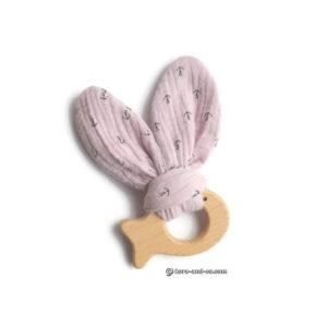 Jouet dentaire pour bébé, oreilles de lapin en tissu rose sur poisson en bois.