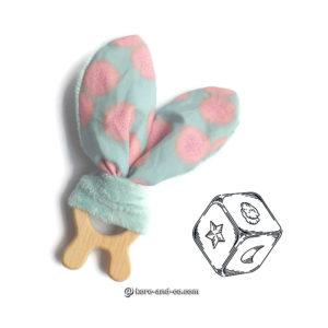 Jouet dentaire pour bébé, oreilles de lapin tissu rose et bleu sur anneau de bois lapin.