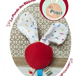 """Jouet d'éveil multi sensoriel sonore pour bébé .Balle rouge, oreilles lapin motifs multicolore. """"Plopi plip""""."""